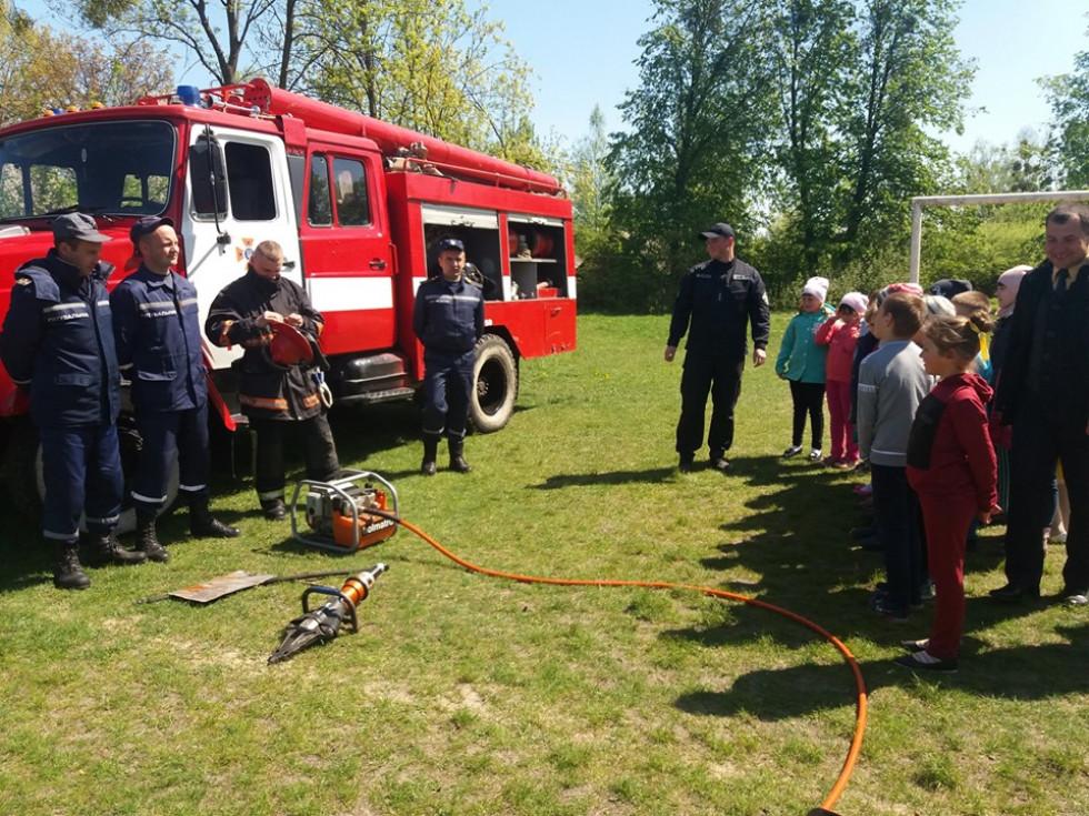 Пожежники показують учням своє спорядження