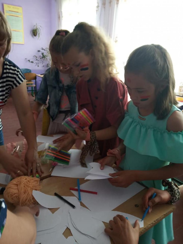Школярі виготовляють корони із паперового пір'я