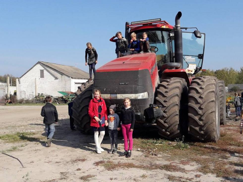 Учні фотографуються біля великої техніки аграрію