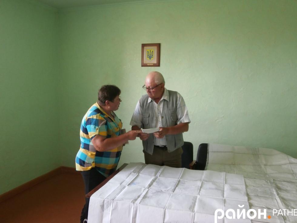 Марія Коцюба показує свої документи на землю колишньому землевпоряднику